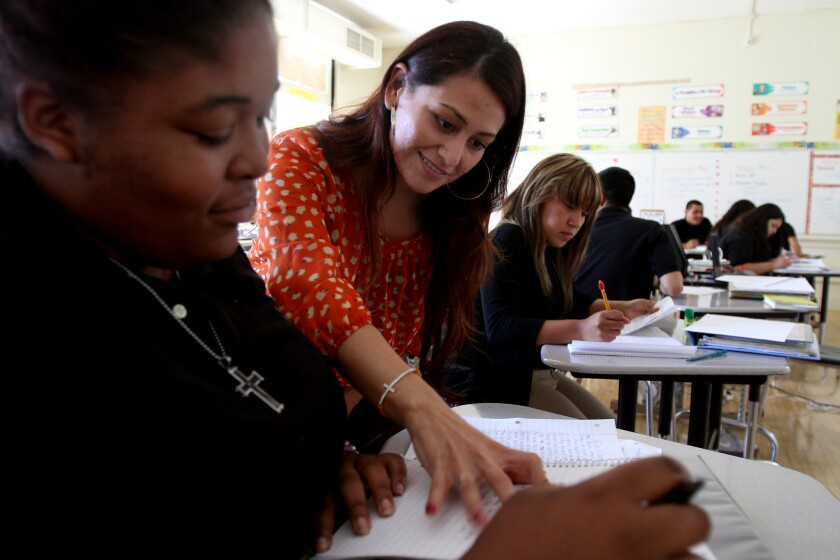Teacher Cassandra Villa, middle, compliments student Anisha Steward of Watts, during English class last year at Animo College Prep on the campus of Jordan High School in Watts. The school is operated by Green Dot, which is expanding into the states of Tennessee and Washington.