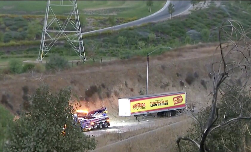 A tow truck waits in front of a big rig's load on a road surrounded by grass and trees.