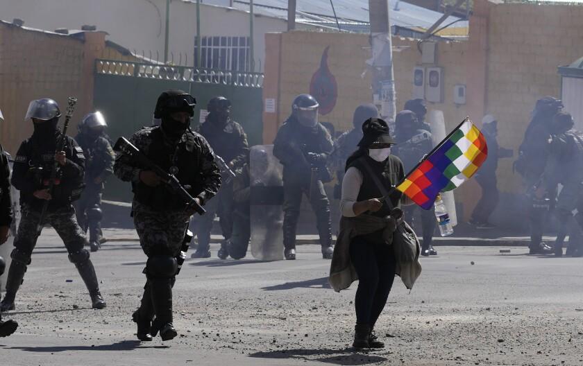 Un cultivador de coca, a la derecha, sostiene una bandera de Whipala durante los enfrentamientos con la policía cerca del mercado de coca en La Paz, Bolivia, el lunes 27 de septiembre de 2021. (AP Foto/Juan Karita)