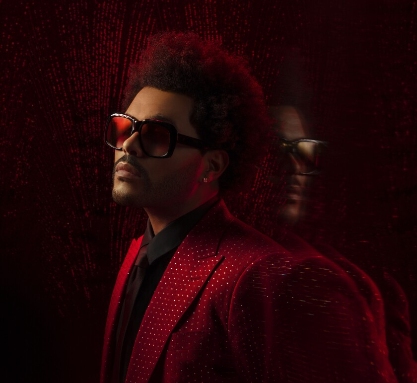 The Weeknd in a red sparkly suit leaning on a mirrored wall