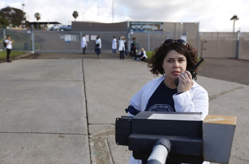 Dr. Bonnie Arzuaga tries to contact the Border Patrol as doctors and other healthcare providers from Doctors for Camp Closure were hoping to get access to give flu shots to detained migrants at the Chula Vista Border Patrol Station in San Ysidro on Dec. 9, 2019.