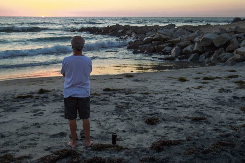 John Hennessy watches the sunset while next to the rock jetty, right, that covers a fuel oil pipeline used to fuel the Encina Power Station in Carlsbad on Tuesday