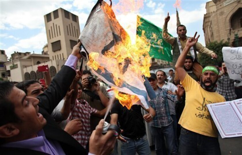 Egyptians chant slogans as a man burns the Israeli flag during an anti-Israel protest held after the Friday noon prayer at Al-Azhar mosque in Cairo, Egypt, Friday, May 10, 2013. Egypt's Muslim Brotherhood staged an anti-Israel rally in Cairo on Friday, the first such protest by the main backers of President Mohammed Morsi since they rose to prominence in the wake of the country's 2011 uprising. (AP Photo/Khalil Hamra)