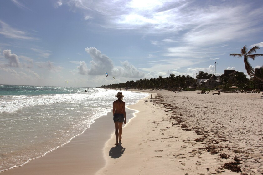 A woman walks along the beach in Tulum, Mexico. Travel from the U.S. to Mexico hit a record high of 25.9 million visitors in 2014, a 24% increase from 2013, according to the U.S. Department of Commerce.