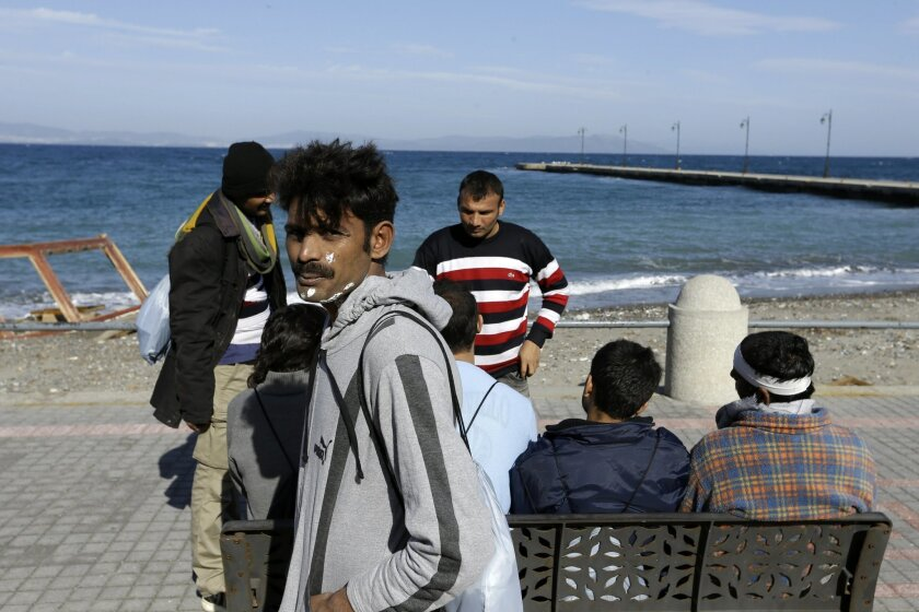 Pakistani migrants wait outside a police station after their registration on the southeastern Greek island of Kos, Thursday, Feb. 18, 2016. European Union leaders are holding a summit on Thursday and Friday amid deep differences over migrant policy. German Chancellor Angela Merkel's open-door stanc