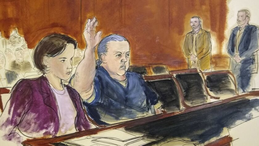 Cesar Sayoc, shown raising his hand in this courtroom artist's rendering, is charged with sending pipe bombs to prominent critics of President Trump. He is expected to plead guilty at a hearing in New York on Thursday, March 21.