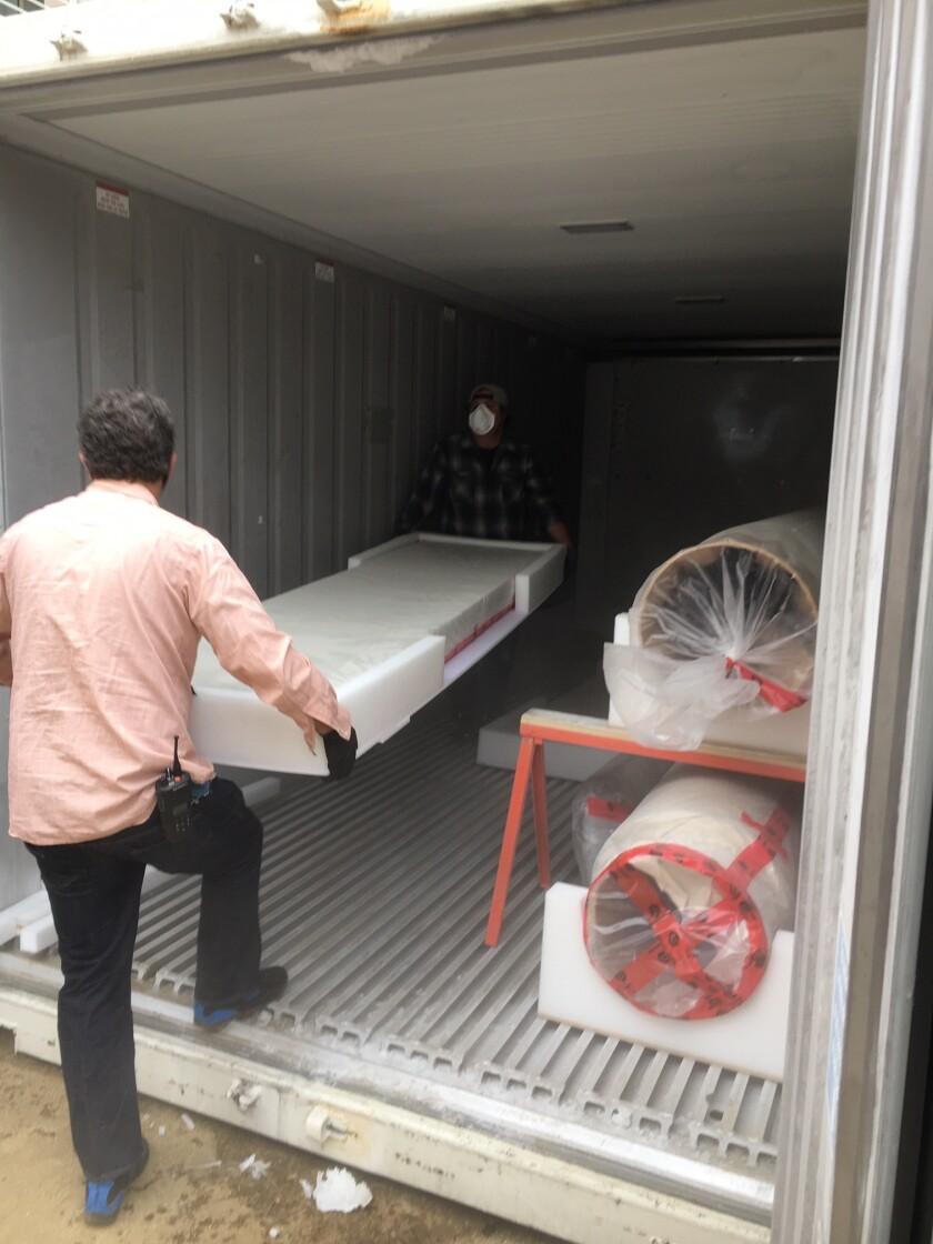 Team members carry a cradled artwork into a mobile freezer.