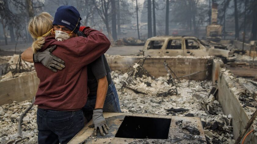 Michael John Ramirez hugs his wife, Charlie, after they found her keepsake bracelet in the rubble of their Paradise, Calif., home that was consumed by the Camp fire.
