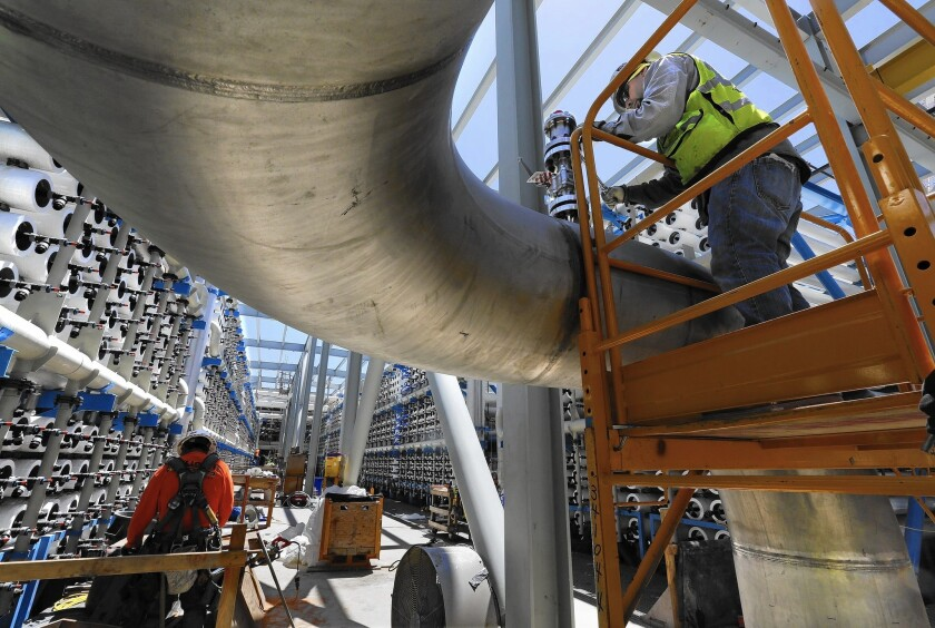 A pipe fitter installs a pressure relief valve on a pipe that will carry desalinated water from the Poseidon Water plant in Carlsbad.