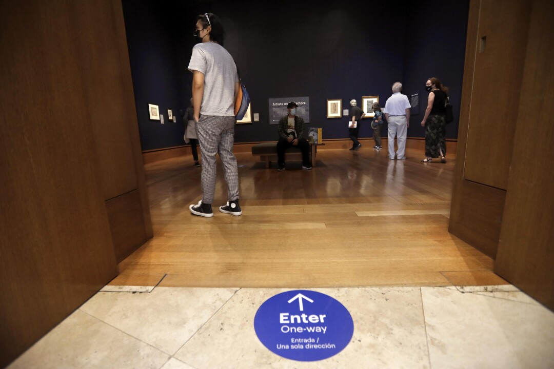 """Visitors take in the new show titled, """"Artists as Collectors."""""""