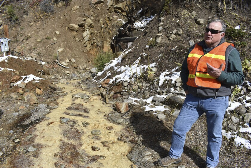 Tillman McAdams with the U.S. Environmental Protection Agency speaks about cleanup work at the Susie mine in Rimini, Mont., on Oct. 12, 2018, as polluted water from the mine flows near his feet. The mine is one of dozens that have fouled water supplies in the mountain community.
