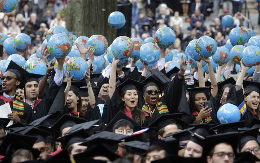 FILE - In this May 30, 2019, file photo, graduates of Harvard's John F. Kennedy School of Government hold aloft inflatable globes as they celebrate graduating during Harvard University's commencement exercises in Cambridge, Mass. Colleges across the U.S. have begun cancelling and curtailing spring graduation events amid fears that the new coronavirus will not have subsided before the stretch of April and May when schools typically invite thousands of visitors to campus to honor graduating seniors. (AP Photo/Steven Senne, File)