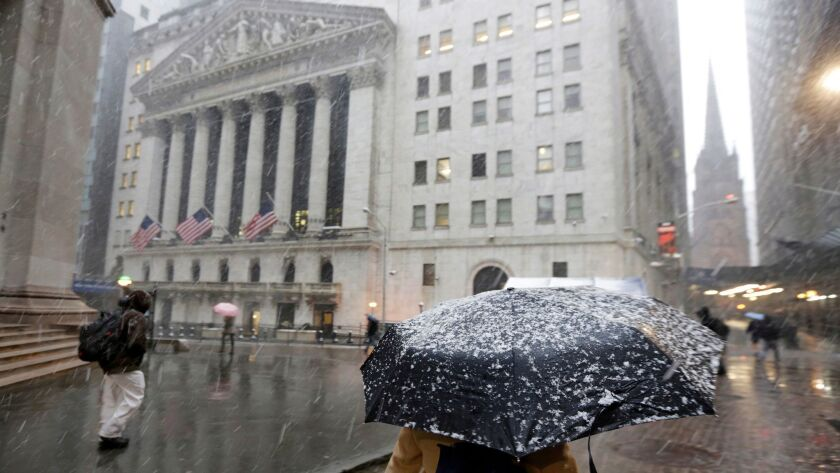 Morning commuters walk through the snow outside the New York Stock Exchange, Monday, April 2, 2018.