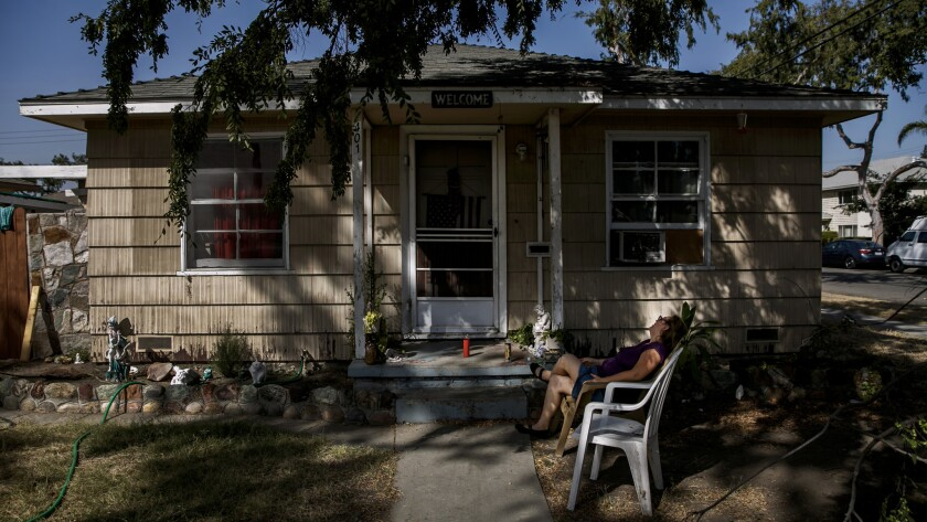 A woman  sits outside the house where police found three people dead.
