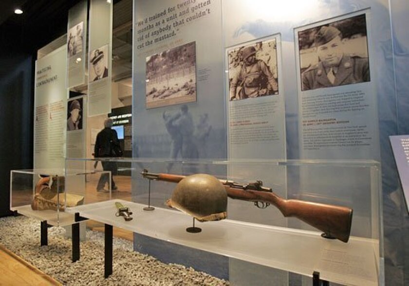 U.S. Army weapons and a helmet are on display at the American Cemetery Visitor Center. (Remy de la Mauviniere / Associated Press)