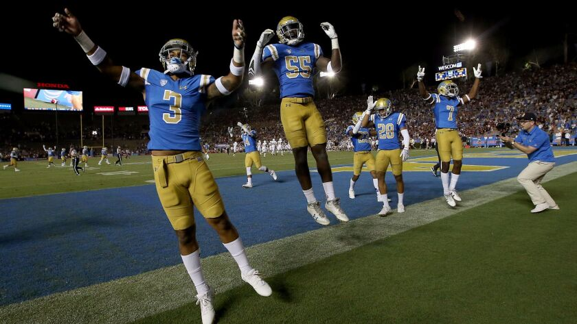 Members of the UCLA football team begin celebrating their 45-44 comeback victory over Texas A&M in the closing moments of the game on Sunday at the Rose Bowl.