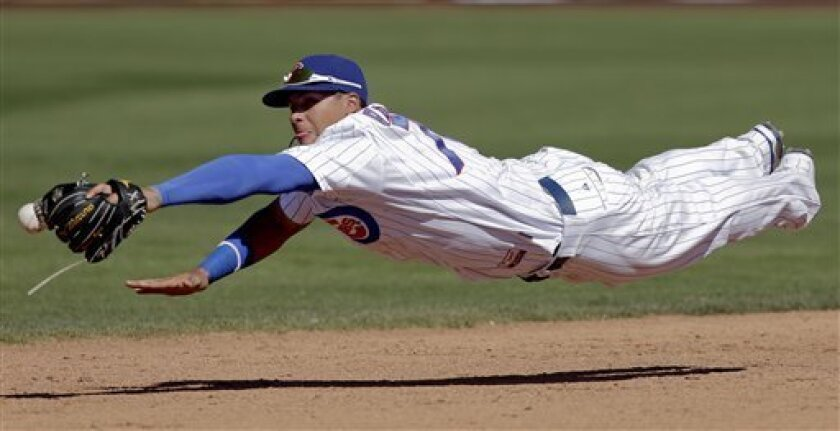 Chicago Cubs shortstop Javier Baez cannot get a glove on a base hit by Colorado Rockies' Eric Young Jr. during the fifth inning of a spring training baseball game in Mesa, Ariz., Wednesday, March 13, 2013. (AP Photo/Chris Carlson)