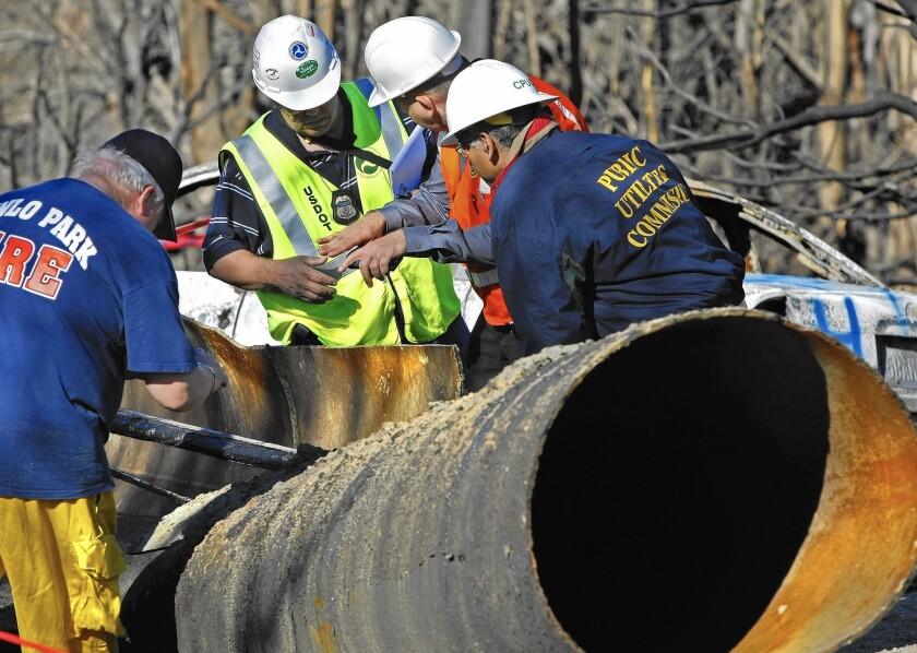 Inspectors from the U.S. Department of Transportation, the California Public Utilities Commission and Pacific Gas & Electric huddle over a section of the 30-inch natural gas pipeline that exploded in San Bruno, Calif. The blast killed eight people, injured 66 and leveled 38 homes.