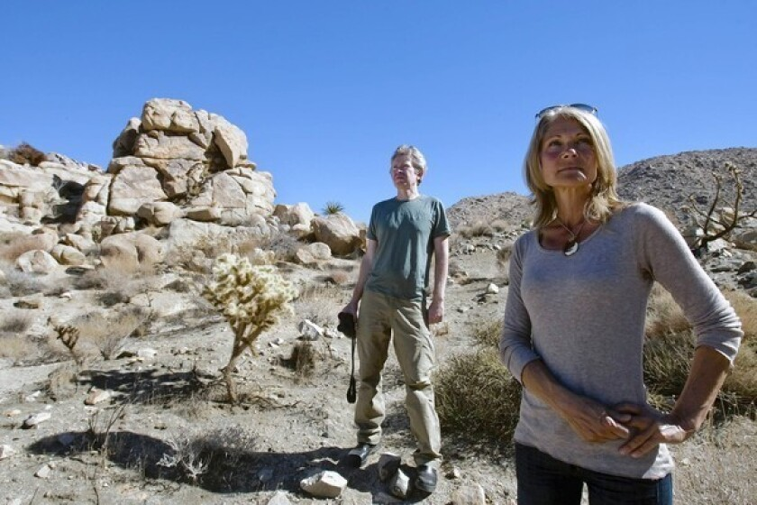 Brendan Cummings, left, senior counsel for the Center for Biological Diversity, and Annica Kreuters look for bobcats on Kreuters' Joshua Tree property. Kreuters has tracked the growth and behavior of visiting bobcats for years.