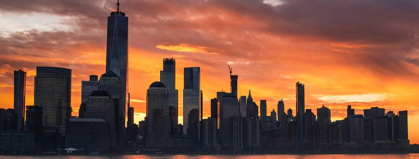 The sun rises behind the New York City skyline, seen from Jersey City, N.J.