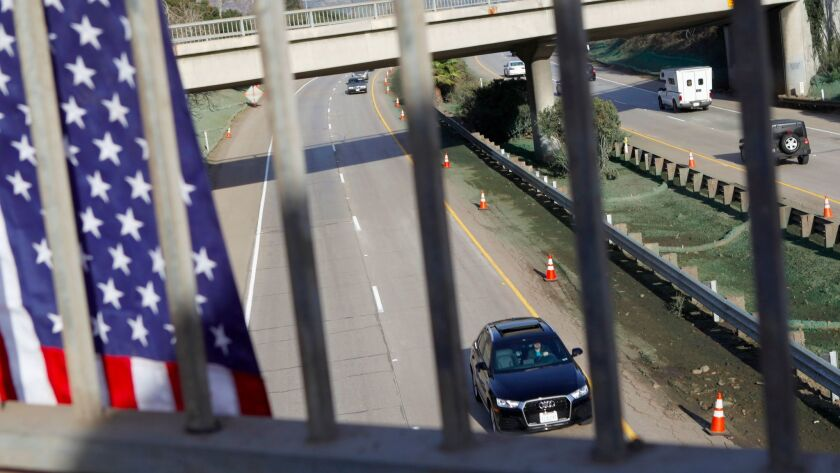 An American flag hangs from Olive Mill Road as cars travel along the reopened Highway 101 in Montecito,