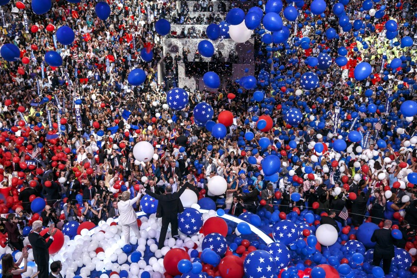 Balloons and confetti fall as Hillary Clinton and Senator Tim Kaine appear before the crowd at the end of the Democratic National Convention in Philadelphia.