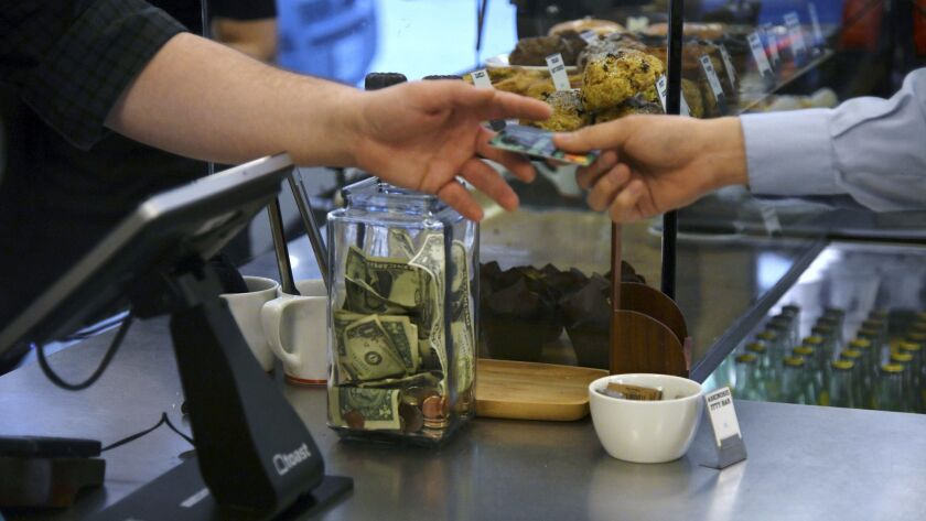 In this June 7, 2018, photo a customer gives their credit card to a cashier at a coffee shop in Chic