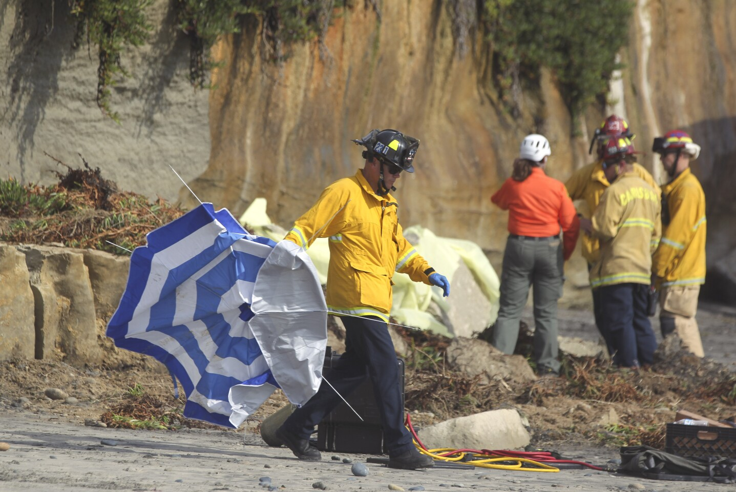 A firefighter carries away a beach umbrella from the area where a section of oceanfront bluff collapsed, background, killing one woman and injuring three just north of the Grandview beach access stairway in Leucadia on Friday, August 2, 2019 in Encinitas, California.