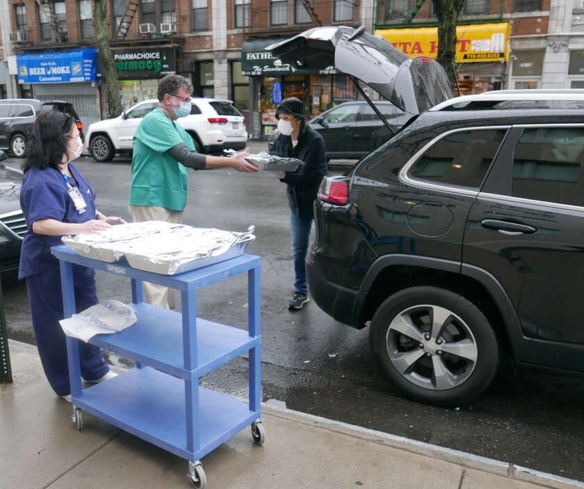 Mt. Sinai Queens ICU secretary Maureen Daly and Dr. Steve Kassapidis receive meals from Michelle Caruso-Cabrera.
