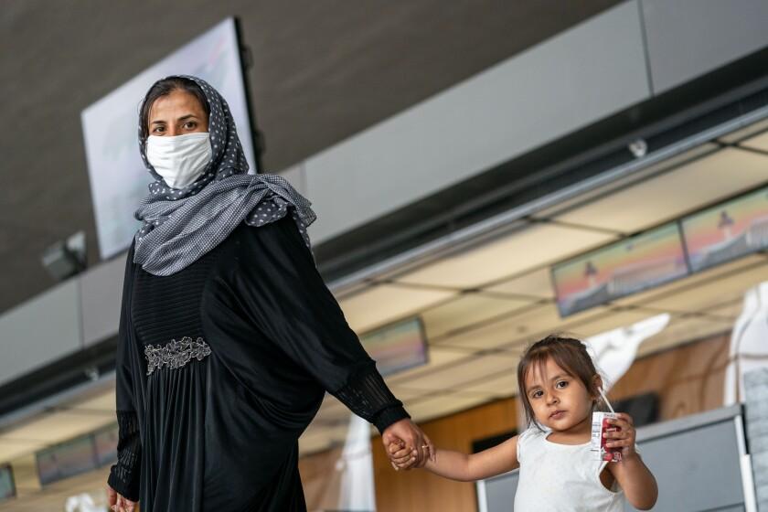 زنی در حالی که دست دختری را گرفته است راه می رود