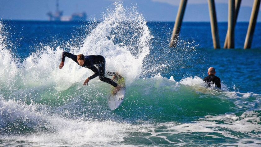 Huntington Beach's Brett Simpson surfs the south side of the Huntington Beach Pier, the site o