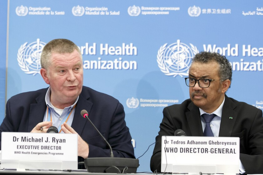 """FILE - In this Monday, Feb. 24, 2020 file photo, Michael Ryan, left, Executive Director of WHO's Health Emergencies programme, next to Tedros Adhanom Ghebreyesus, right, Director General of the World Health Organization (WHO), addresses a press conference about the update on COVID-19 at the World Health Organization headquarters in Geneva, Switzerland. The emergencies chief of the World Health Organization said on Monday March 1, 2021, it was """"premature"""" and """"unrealistic"""" to think the pandemic might be stopped by the end of the year, but that the recent arrival of effective vaccines could at least help dramatically reduce hospitalizations and death. (Salvatore Di Nolfi/Keystone via AP, File)"""