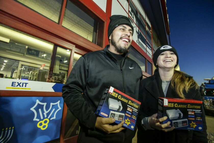 Greg Mayorga, left, and Deysi Flores are jubilant after purchasing one of only 57 units of retro-looking Nintendo NES Classic at Best Buy in Atwater Village.