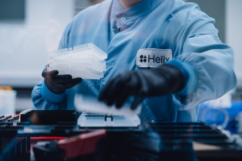 A Helix lab technician gathers trays at the company's high complexity clinical testing lab in San Diego.