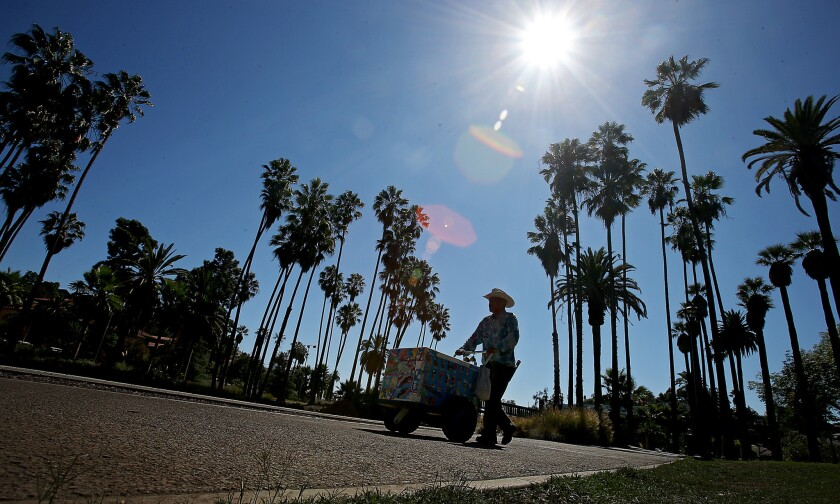 An ice cream vendor pushes a cart on the sidewalk that rings Echo Park Lake in Echo Park.