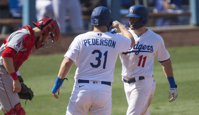 Dodgers center fielder AJ Pollock celebrates his two-run home run with Joc Pederson.