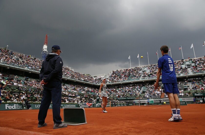 A menacing sky looms over center court as France's Kristina Mladenovic, center, and Serena Williams of the U.S. play their third round match of the French Open tennis tournament at the Roland Garros stadium in Paris, France, Saturday, May 28, 2016. (AP Photo/Christophe Ena)