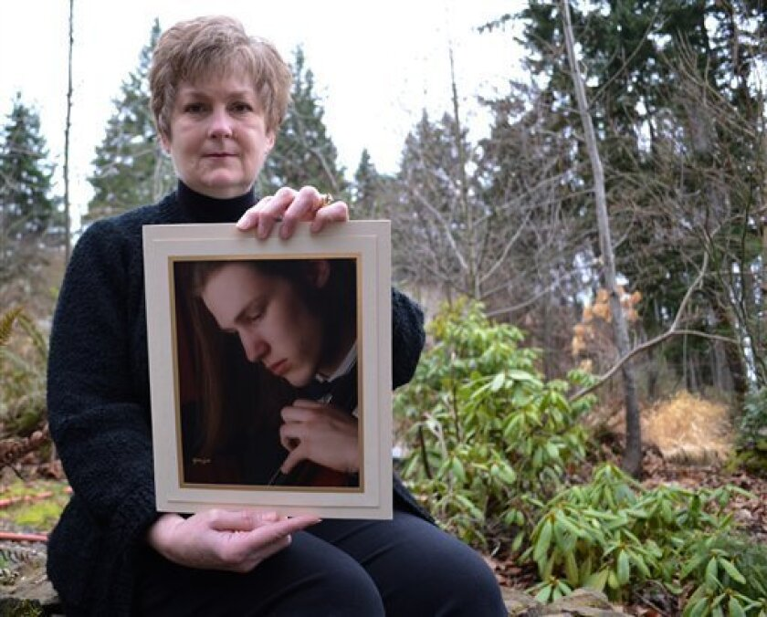 In this Feb. 16, 2013 photo, Karen Williams poses with a photo of her deceased son, Loren, in Beaverton, Ore. Williams, who battled Facebook over the right to view Loren's Facebook page, has been urging lawmakers for years to do something to prevent others from losing photos, messages and other mem