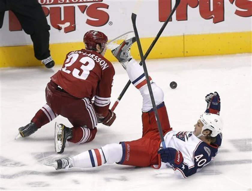 Columbus Blue Jackets' Jared Boll (40) and Phoenix Coyotes' Oliver Ekman-Larsson (23) battle for the puck during the second period of an NHL hockey game, Saturday, Feb. 16, 2013, in Glendale, Ariz. (AP Photo/Matt York)
