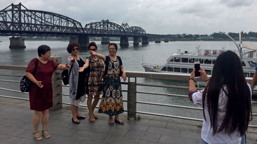 Chinese tourists pose alongside the Yalu River in Dandong, China, with North Korea in the background