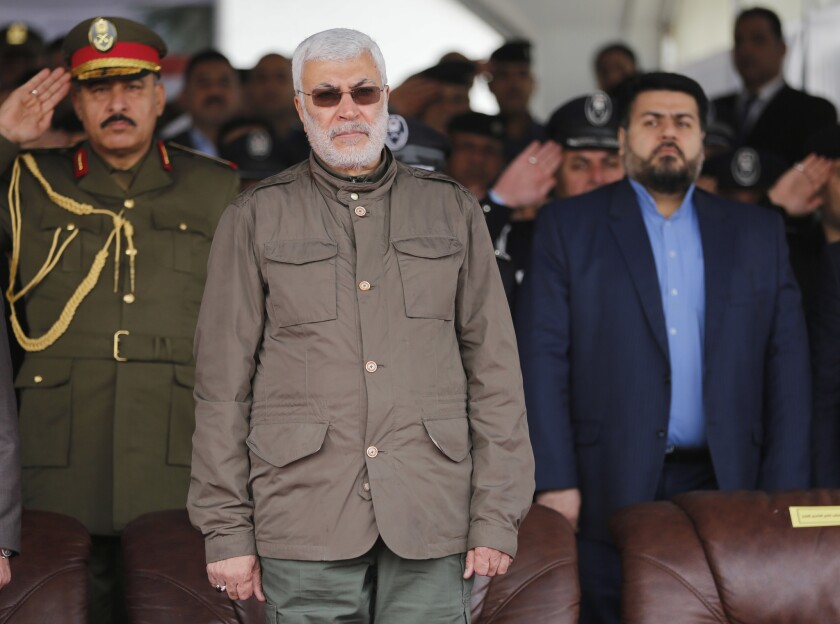 In this Jan. 9, 2016 file photo, Abu Mahdi al-Muhandis, center, attends a ceremony marking Police Day in Baghdad, Iraq.