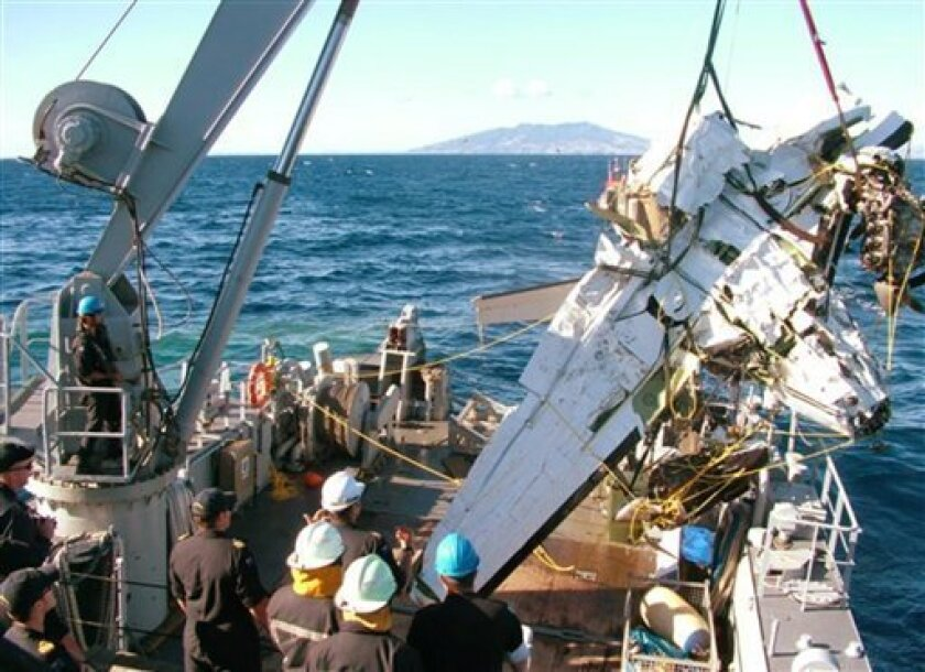 In this Sunday, April 7, 2013 photo released by the New Zealand police, the wreckage of a small plane carrying American wireless executive Eric Hertz and his wife Kathy that crashed into the ocean near Kawhia Harbour, about 150 kilometers (93 miles) south of Auckland, is lifted onto the deck of HMNZS Manawanui. Navy divers recovered the bodies of Hertz and his wife after their plane crashed into the ocean. (AP Photo/New Zealand Police via The New Zealand Herald) NEW ZEALAND OUT, AUSTRALIA OUT