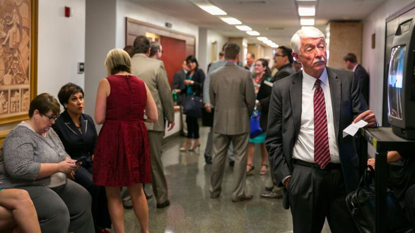 There are more than 1,800 registered lobbyists seeking to influence California government, some of them seen here in the hallway of the State Capitol, in Sacramento last fall.