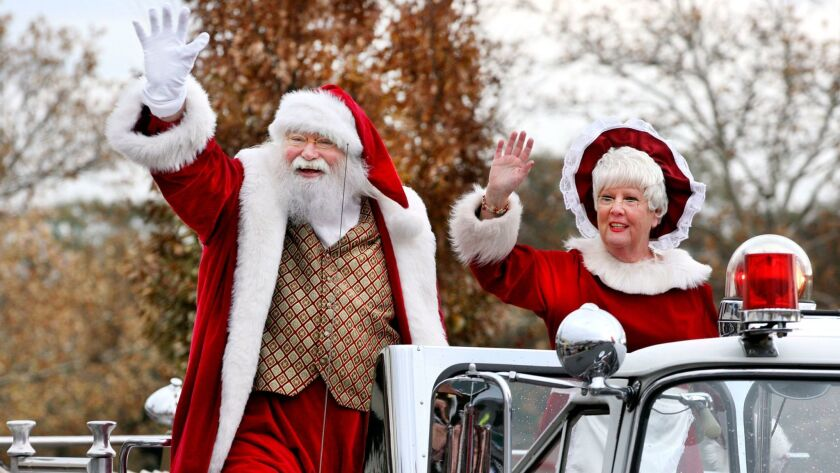 Santa Claus and Mrs. Claus arrived riding atop a fire engine during a celebration held at the Apple
