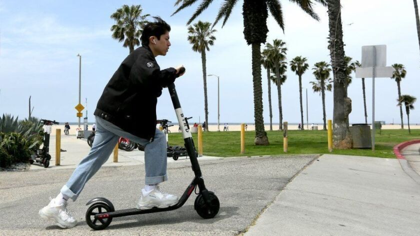 A Bird customer rides a scooter near the beach in Venice.
