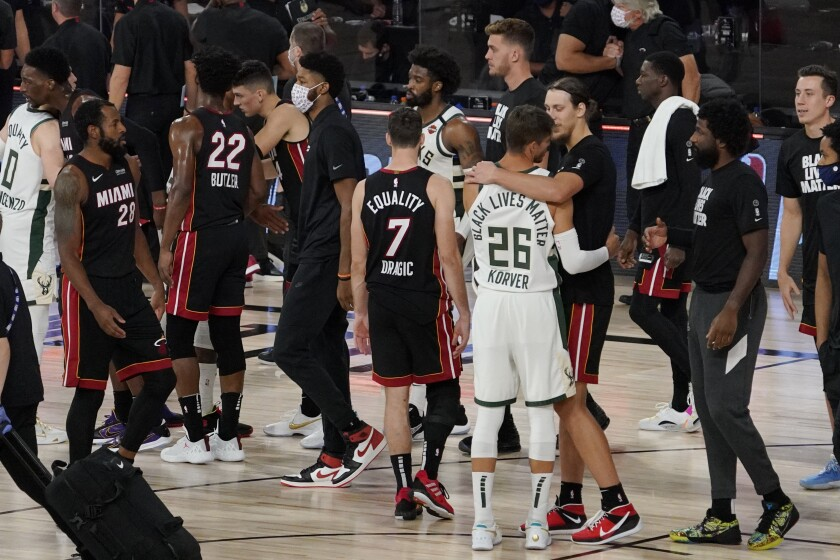 Miami Heat's Kelly Olynyk, right, and Milwaukee Bucks' Kyle Korver (26) embrace following their NBA conference semifinal playoff basketball game Tuesday, Sept. 8, 2020 in Lake Buena Vista, Fla. Miami won the game and eliminated the Bucks from the playoffs. (AP Photo/Mark J. Terrill)