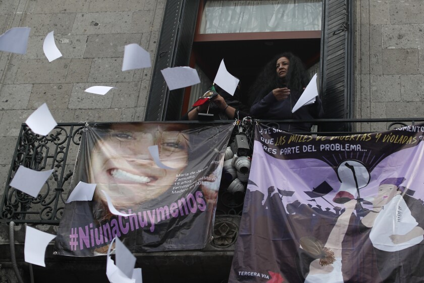 Gender violence activist Yesenia Zamudio throws papers out a window at Mexico's National Human Rights Commission office.