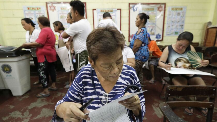 A Filipino checks her ballot as she votes at a polling center at the Manuel L. Quezon elementary sch