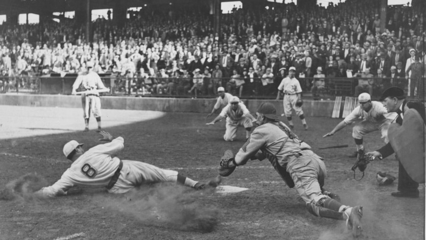 This 1939 photo by Times staff photographer Jack Herod of a runner sliding into home plate at a Holl