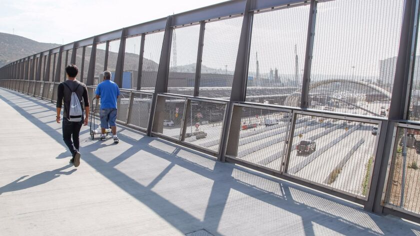 Pedestrians cross the bridge at the San Ysidro Land Port of Entry modernization and expansion project, west of Interstate 5 and west of the port of entry.